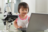 Genius litlle girl with laptop and microscope poster