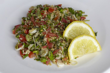 Lebanese Tabbouleh with two lemon slices on a white plate.