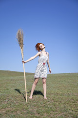 Young witch with broom at field