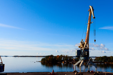 sea port cranes with blue cloudy sky in background and water in