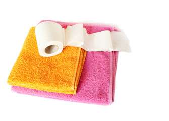 The roll to a toilet paper lies on a pile of towels