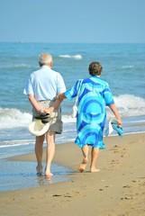 Coppia di anziani che passeggiano sulla riva del mare