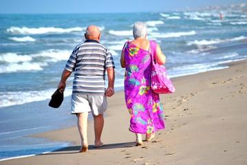Anziani che passeggiano sulla riva del mare