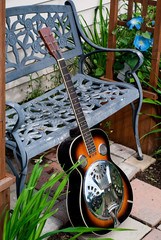 Dobro Style Guitar Leaning against Metal Bench