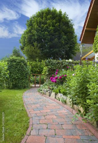 Leinwandbild Motiv Garten mit Blumenbeet und Gartenweg eines Einfamilienhauses