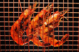 Barbecued shrimp in a cooper grilling rack ready to eat. poster