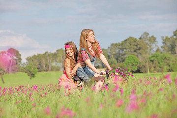 happy girls on bicycle in summer