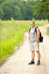 Full length portrait of a young man hiking into the woods