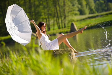 Happy romantic woman sitting by lake splashing water