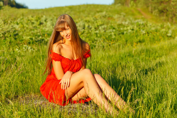 Pretty caucasian woman in a red dress sitting on a green meadow