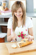 Delighted woman cutting bread in the kitchen