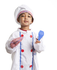 Toddler dressed as a cheg holding an oven mitt and spatula