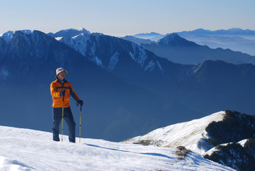 asian mountaineer stand on snow mountain .