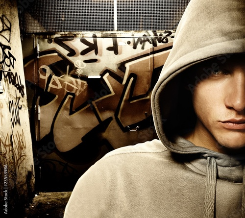 Cool looking hooligan in a graffiti painted gateway