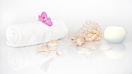 Muscheldekoration mit Orchidee, Handtuch und Kerze