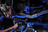Dramatically lightened mechanic working under a car