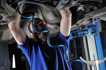 Auto mechanic working under the car - a series of MECHANIC