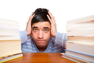 Junger müder frustrierter Student lernt mit Büchern auf Prüfung