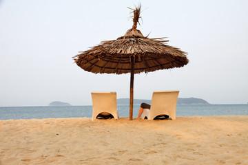 Sonnenschirm mit Strandliegen an einem einsamen Strand