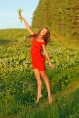 Jumping pretty brunette girl against summer meadow