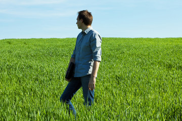 young man standing with a laptop in the green field