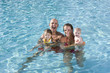 Portrait of young family smiling in swimming pool