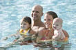 Family with baby and toddler in swimming pool