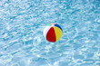 Beach ball floating on surface of swimming pool