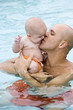 Father giving baby kiss in swimming pool