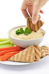 Hand dipping pita in hummus