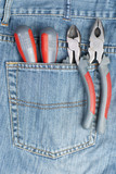 two screwdriver, nippers and pliers in the pocket of jeans poster