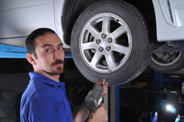 Car mechanic removing wheel nuts - a series of MECHANICAL