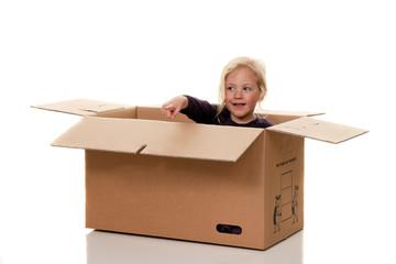 Kind in Umzugskarton. Liegt beim Umzug in Schachtel.