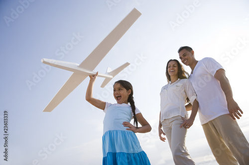 Hispanic family and girl having fun with toy plane