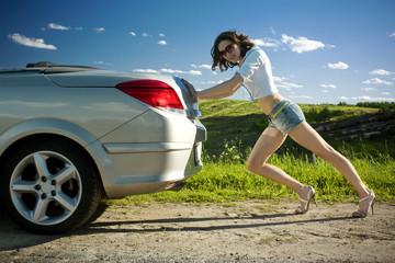Woman is pushing broken car
