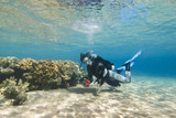 Young female scuba diver in clear shallow water.