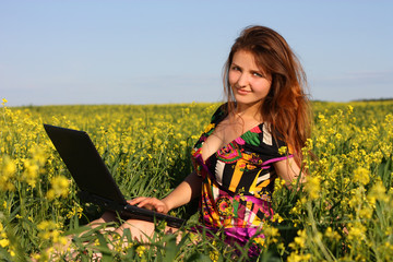 Beautiful brunette in a yellow meadow with laptop