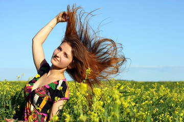 Beautiful young girl on the yellow meadow. Wind hair