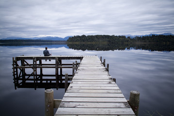 Fisherman sitting on a jetty on a moody winters day