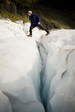 Man crosses a deep crevasse on Fox Glacier, New Zealand