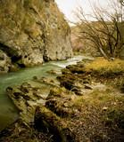 Small stream running between a rock face and an embankment poster