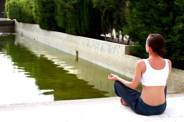 Woman meditating by the water in the park
