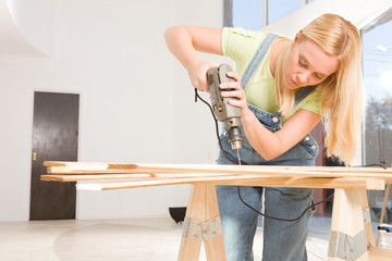 Attractive woman drilling