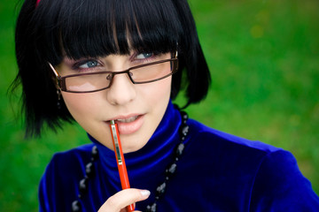 young thinking woman in glasses with pen