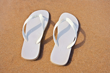 white flip flops on sand beach