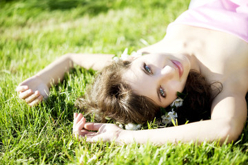 Beautiful girl lying on the grass with flowers