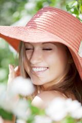 Beautiful woman among flowering gardens