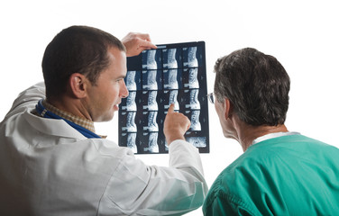 Two Doctors Examining Patient's Spinal Film Scans