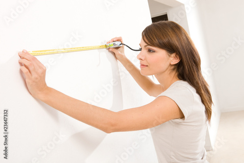 Girl measuring wall