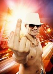 Man showing middle finger in front of night city